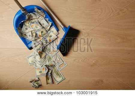 Broom sweeps dollars in garbage scoop on wooden floor background