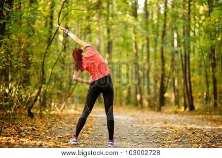 woman exercising in park, stretching hands up