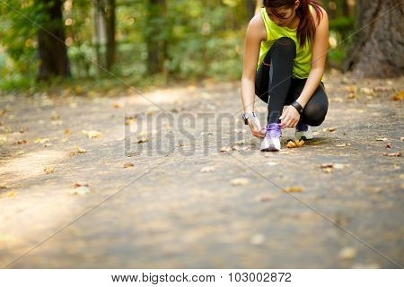 young woman runner tying shoelaces in park