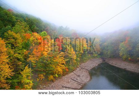 Fog over small lake in autumn time