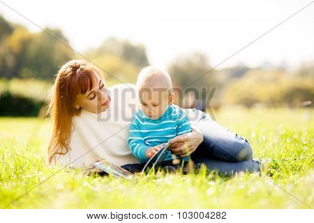 Mother with boy reading book in park, beautiful sunset light