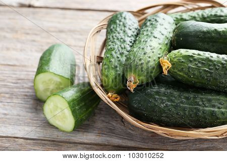 Fresh Cucumbers In Basket On Grey Wooden Background