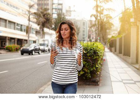 Beautiful Woman Using Smart Phone While Walking