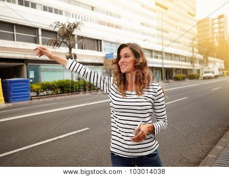 Cheerful Young Woman Hailing A Cab On City Street