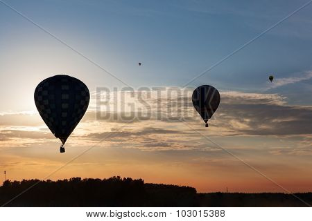 Silhouettes of flying balloons on the sunset sky