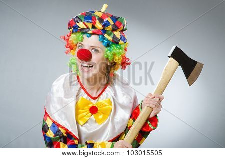 Clown with axe in funny concept