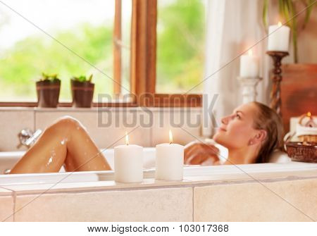 Soft focus photo of gentle young woman lying down in bath tub with foam and candle, enjoying spa procedure in the luxury resort