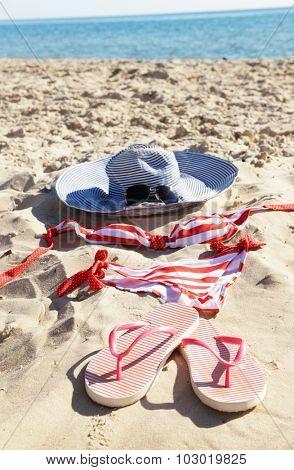 Flip flops, swimsuit and hat on beach sand closeup