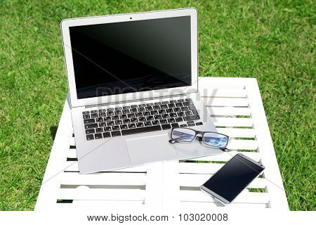 Laptop, smartphone and glasses on wooden table outdoor