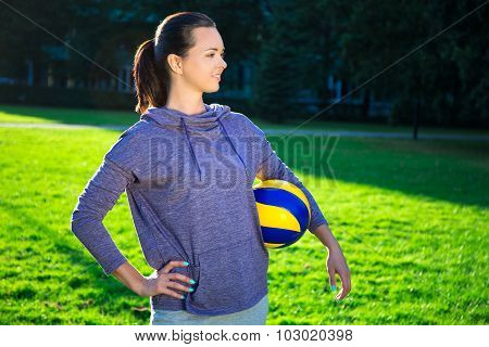 Happy Slim Woman In Sportswear With Ball In Park