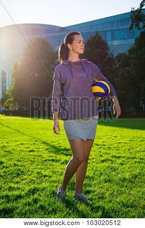 Portrait Of Happy Slim Woman In Sportswear With Ball In Evening Park