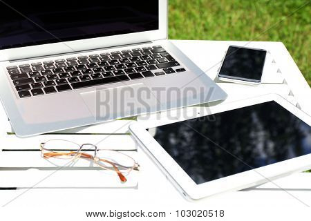 Gadgets on wooden table outdoor