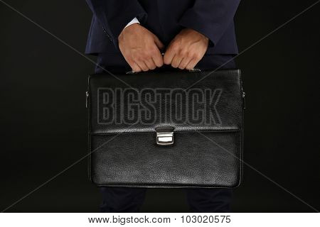 Elegant man in suit with briefcase on dark background