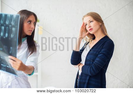 Doctor woman with white labcoat looking at x-ray radiographic results ct scan mri in  hospital clini