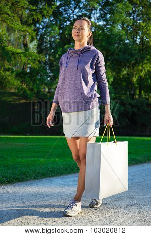 Happy Young Slim Woman In Sportswear Walking In Park With Shopping Bags
