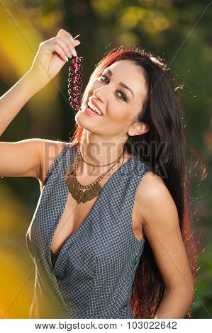 Beautiful woman in gray posing in autumnal park holding a ripe grapes bunch. Young brunette woman