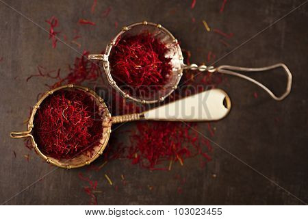 saffron spice threads and powder  in vintage  old sieve,  old metal background, closeup
