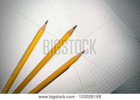 Pencils on a checkered notebook