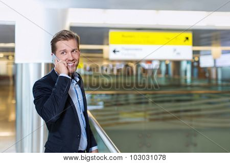 Young businessman speaking on the phone at the airport