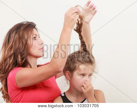 Mother Combing Hair For Daughter