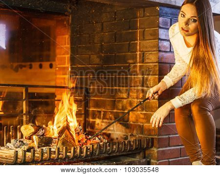 Woman With Fire Iron Poker At Home Fireplace.
