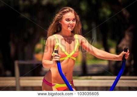 Blonde Girl In Bikini Trains On Stepper On Sports Ground
