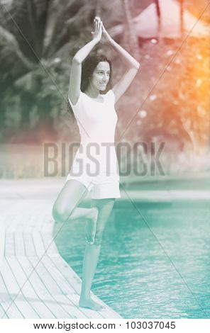 Artistic filtered portrait of a woman practising yoga balancing on one foot at the edge of a pool, greyscale with azure and sun flare effects