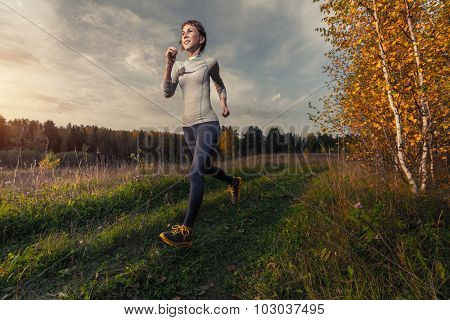 Slim lady running in the autumn forest