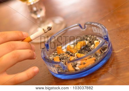 Hand Holding Cigarette Over An Ashtray