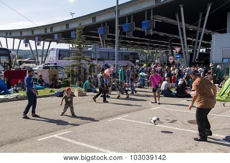 BREGANA, SLOVENIA: SEPTEMBER 19, 2015: Group of refugees from Middle East and North Africa at Bregana, state border between Slovenia and Croatia.Two men playing football with little boy.