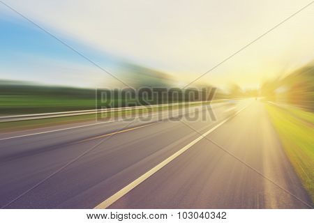 Empty Asphalt Road In Motion Blur And Sunlight With Vintage Tone.