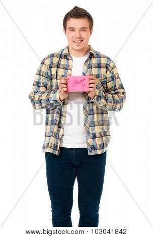 Young man gives a present wrapped in pink gift paper, isolated on white background