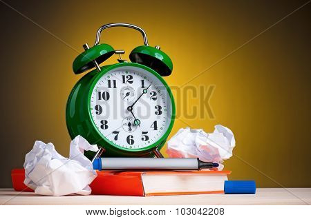 Big green alarm clock with red book and crushed paper on dark yellow background