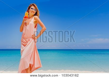 outdoor portrait of young smiling beautiful woman with bright cocktail on tropical sand beach