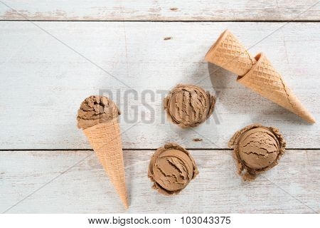 Top view cocoa ice cream in waffle cone on rustic wooden background.