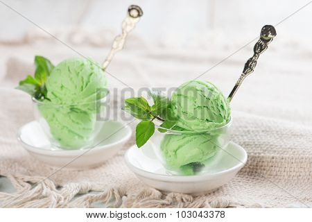 Scoop of honeydew ice cream in cup on wooden vintage background.