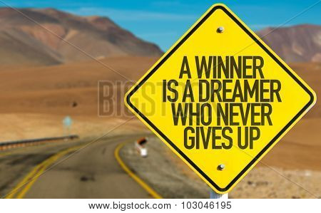 A Winner Is A Dreamer Who Never Gives Up sign on desert road