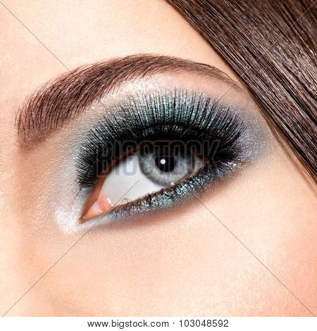woman's eye with turquoise makeup. Long false eyelashes. macro shot
