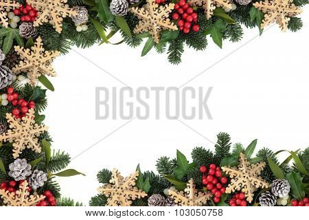 Christmas abstract background border with snowflake bauble decorations, holly, ivy and fir on parchment paper over old oak wood.