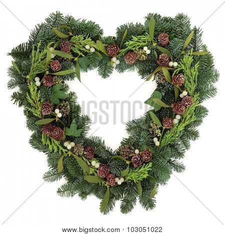 Christmas heart shaped wreath with mistletoe, ivy, pine cones and winter greenery over white background.