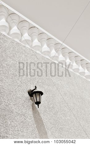 Retro style terrace railing in perspective. A classic lamp mounted on the wall. outdoor shot.