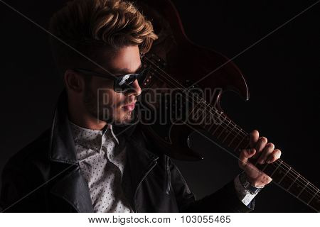 closeup portrait of a young guitarist holding his electric guitar next to his head on on dark background