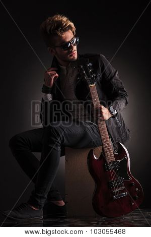 side view of a young guitarist sitting and looking back while he holds his electric guitar , against black studio background