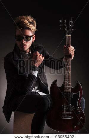 serious guitarist wearing sunglasses is sitting and holding his electric guitar, against black studio background