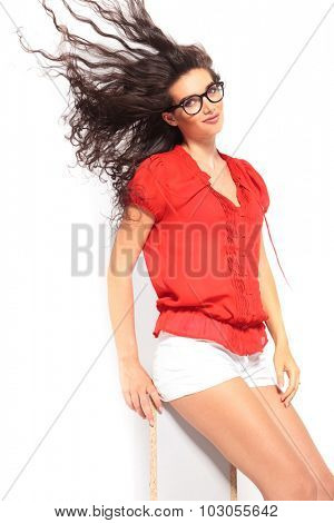 smart beautiful girl sitting on a chair and posing while wind is blowing her hair up