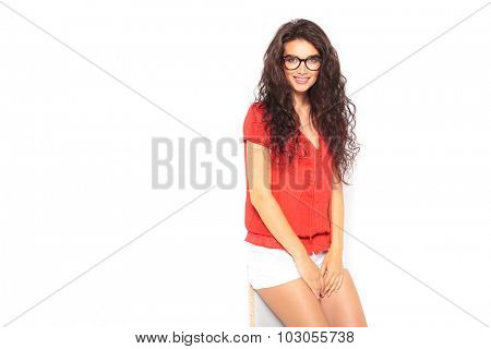 cute smart girl leaning against the wall while smiling at the camera with hands on her legs