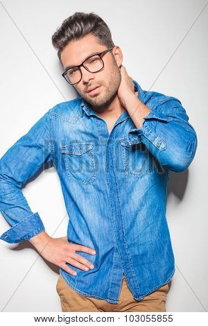 close up with young beautiful man wearing denim shirt while touching his neck
