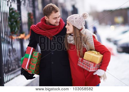 Young couple with giftboxes talking while walking home on Christmas eve
