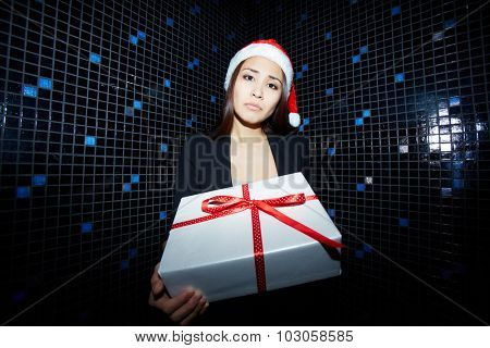 Unhappy businesswoman with giftbox looking at camera in night club