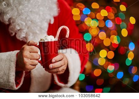 Tasty latte with whipped cream and candy cane in Santa hands